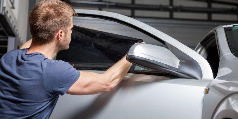 Pracownik agencji reklamowej okleja auto